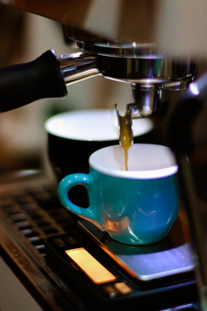 photography of espresso maker filling cups